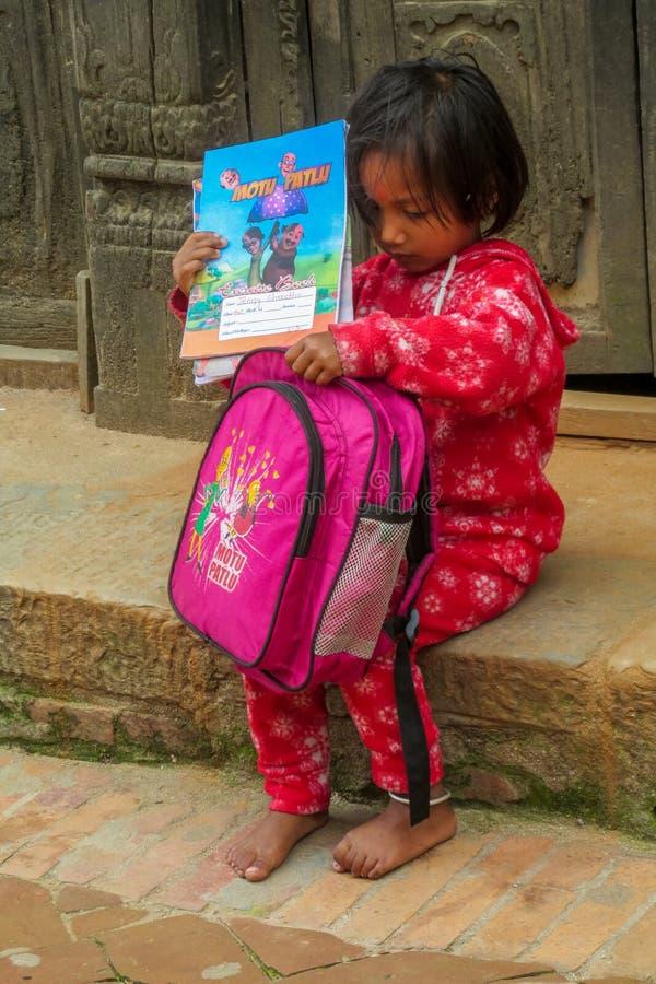 La niña del Nepali con los libros y la pequeña escuela hacen excursionismo foto de archivo libre de regalías