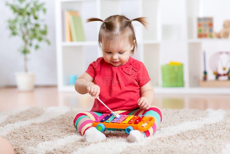 La niña del niño toca un instrumento musical foto de archivo libre de regalías