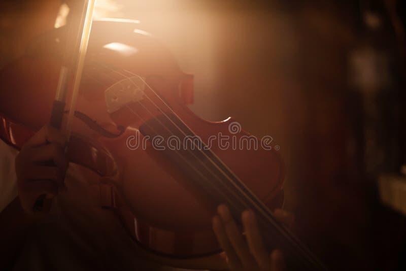 La niña del tiro del primer que jugaba a la orquesta del violín instrumental con tono caliente y oscuridad y grano del efecto lum foto de archivo