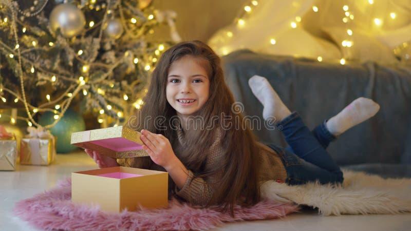 La niña desempaqueta los regalos de la Navidad fotografía de archivo