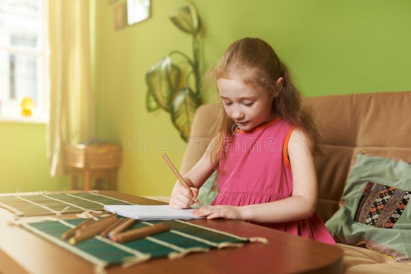 La niña dibuja el lápiz en el cojín foto de archivo libre de regalías