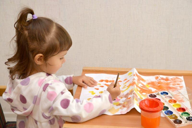 La niña dibuja las pinturas del color de agua imagen de archivo