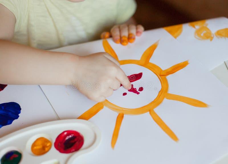 La niña dibuja las pinturas el sol foto de archivo libre de regalías