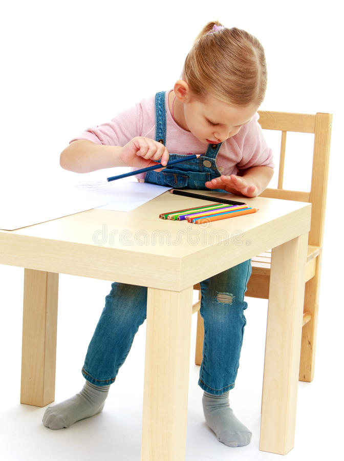 La niña dibuja los lápices que se sientan en la tabla foto de archivo