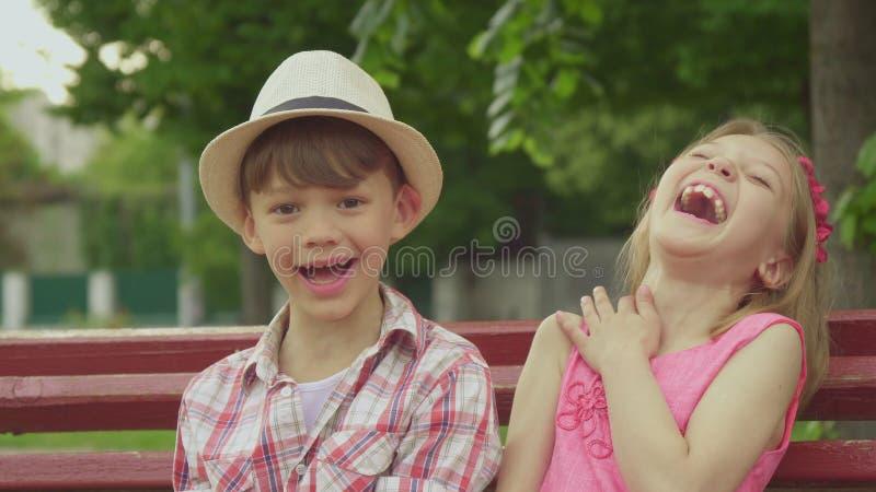 La niña dice algo al muchacho en el banco fotografía de archivo
