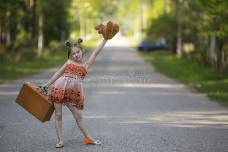 La niña divertida con la maleta y el oso de peluche está en el camino Viajes foto de archivo