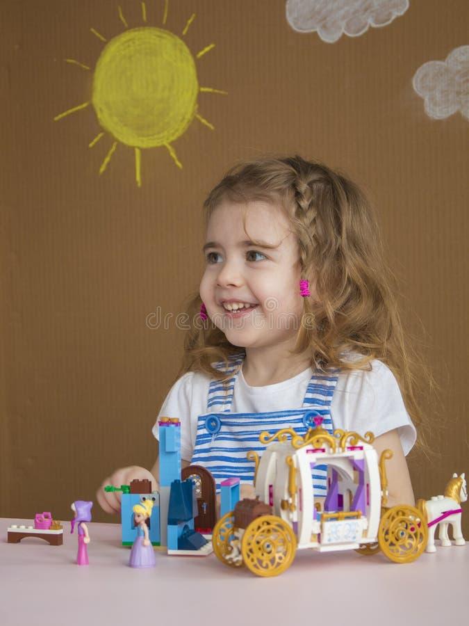 La niña divertida linda del preescolar que juega con el juguete de la construcción bloquea la construcción de una torre en sitio  fotografía de archivo libre de regalías
