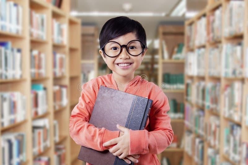 La niña divertida lleva a cabo la literatura en la biblioteca fotos de archivo