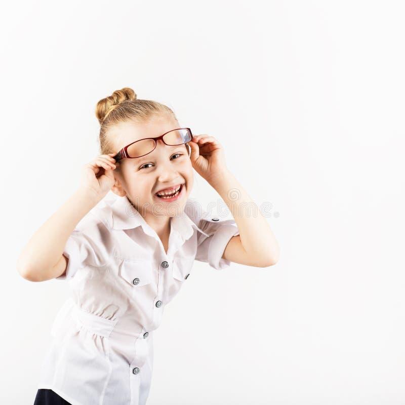 La niña divertida que lleva las lentes imita a un profesor estricto a imagen de archivo
