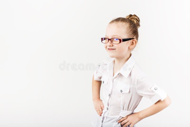 La niña divertida que lleva las lentes imita a un profesor estricto a foto de archivo libre de regalías
