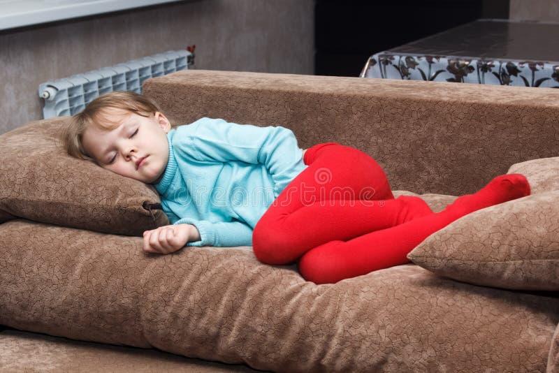 La niña duerme como un top en el sofá foto de archivo libre de regalías