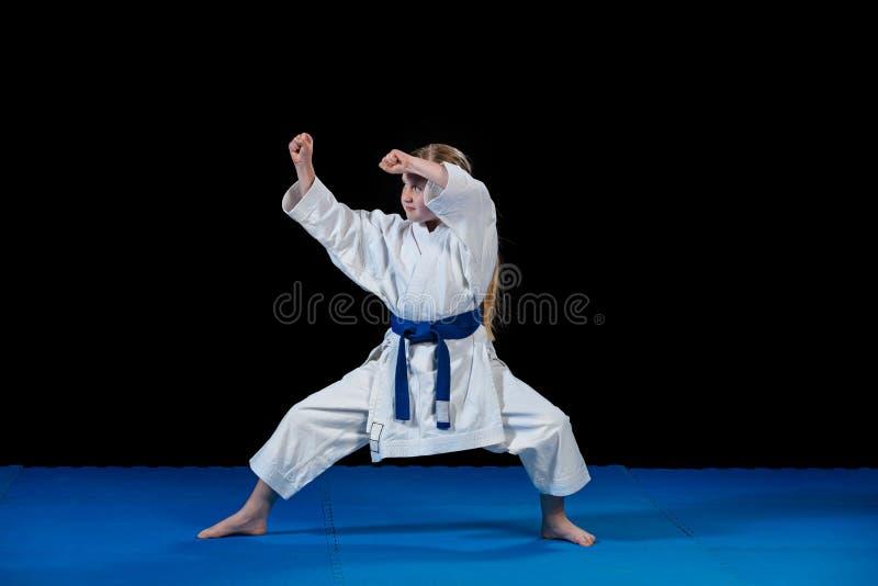 La niña dulce en artes marciales practica como el niño del karate solamente aislado en fondo negro fotografía de archivo libre de regalías