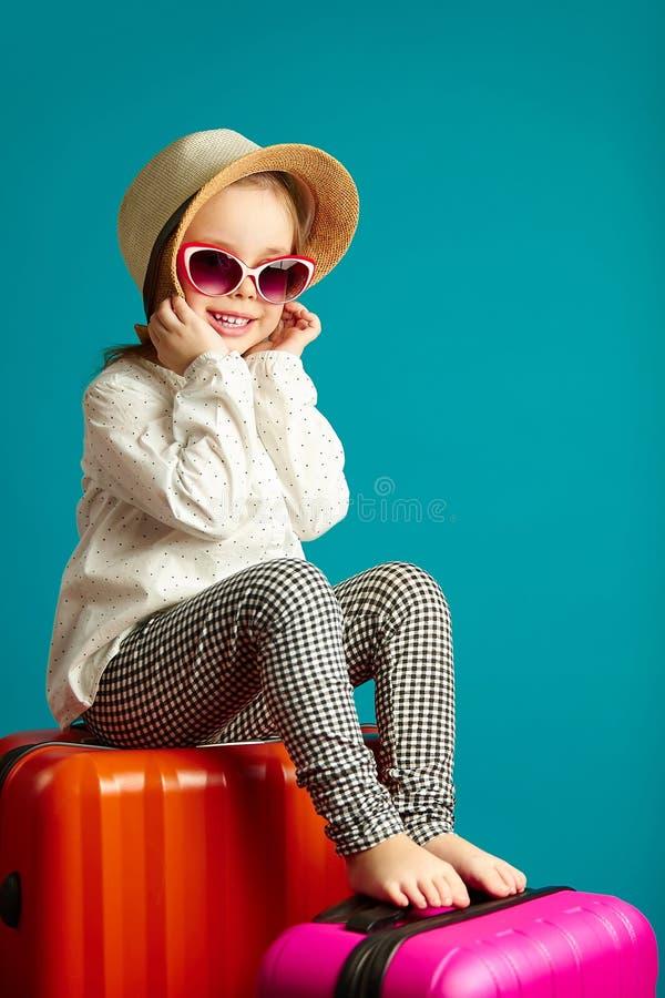 La niña dulce se sienta en las maletas, para viaje que espera, retrato del niño feliz en azul aislado fotos de archivo libres de regalías