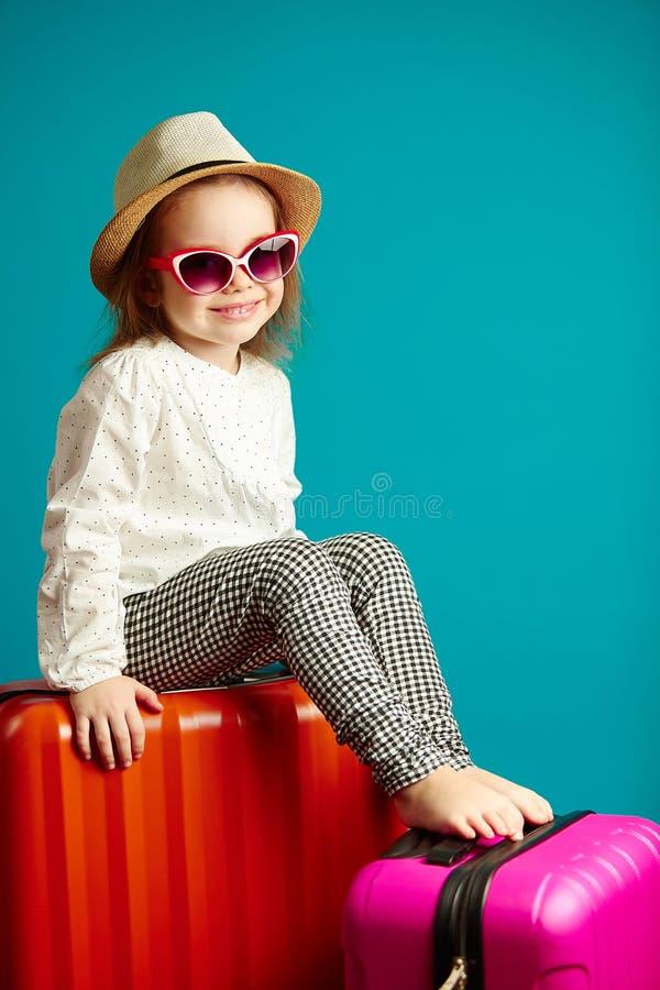 La niña dulce se sienta en las maletas, para viaje que espera, retrato del niño feliz en azul aislado imagen de archivo