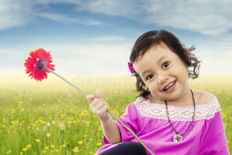 La niña dulce sostiene la flor en el campo foto de archivo