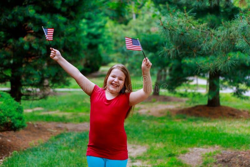 La niña elemental feliz de la edad sonríe mientras que sostiene la bandera americana en su jardín en el cuarto de julio Día de la imagenes de archivo