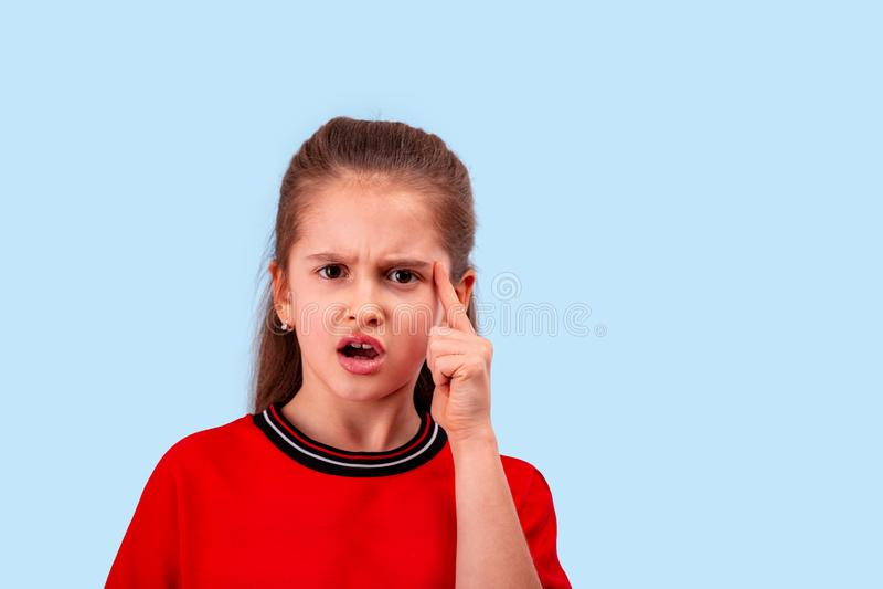 La niña emocional clama contra del ultraje o del descontento que se sostiene el dedo índice en el templo fotografía de archivo libre de regalías