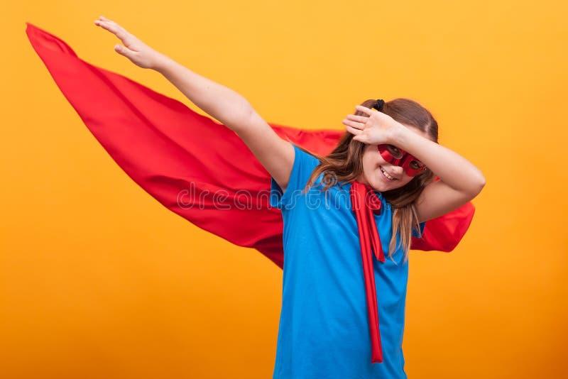 La niña en cabo rojo juega al super héroe en estudio sobre fondo amarillo foto de archivo