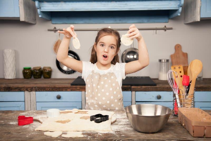 La niña en la cocina está haciendo las galletas fuera de la pasta con diversas formas en la cocina Poco ayudante, hecho en casa foto de archivo