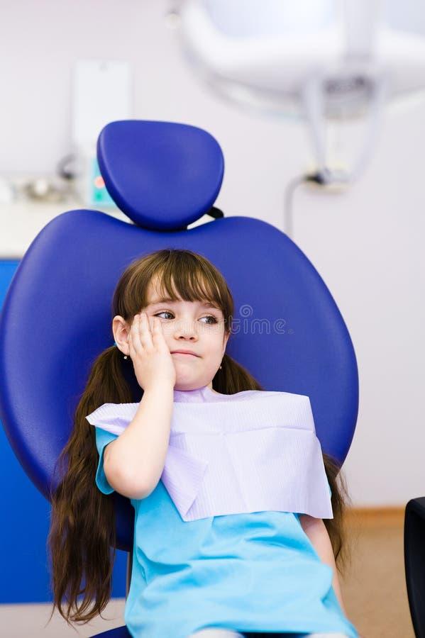 La niña en el dentista se queja de dolor de muelas imagenes de archivo