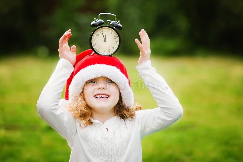 La niña en el sombrero de Papá Noel con el reloj tiene una Navidad fotos de archivo libres de regalías