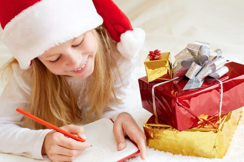 La niña en el sombrero de Papá Noel escribe la letra a Papá Noel fotografía de archivo libre de regalías
