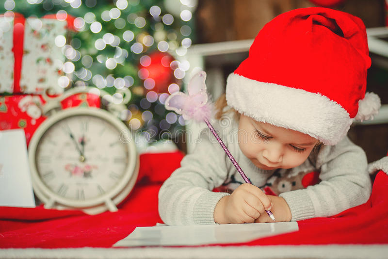 La niña en el sombrero de Papá Noel escribe la letra a Santa Claus imagen de archivo