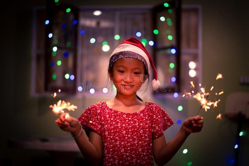 La niña en el sombrero de Papá Noel goza para celebrar Nochebuena fotografía de archivo