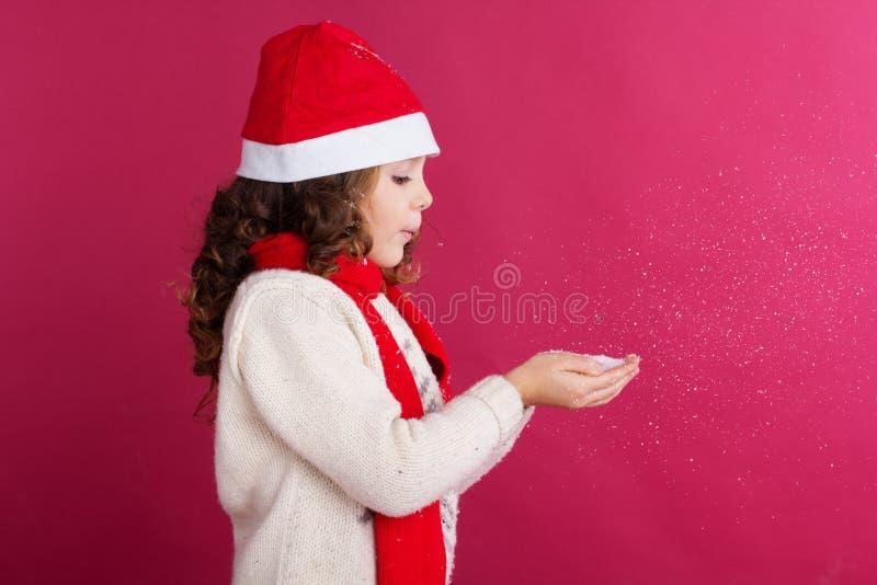 La niña en el sombrero de santa está sosteniendo nieve falsa fotos de archivo