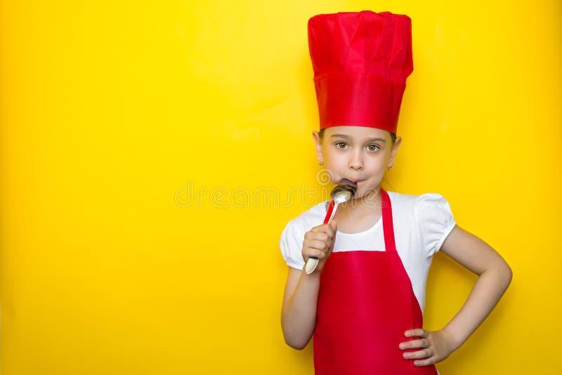 La niña en el traje de un cocinero rojo lame la cuchara, gusto delicioso, en fondo amarillo con el espacio de la copia fotos de archivo