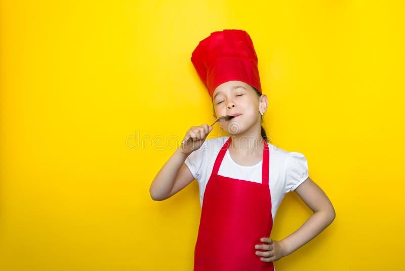 La niña en el traje del cocinero lame la cuchara, cerrándose los ojos, gusto delicioso, en fondo amarillo con el espacio de la co foto de archivo