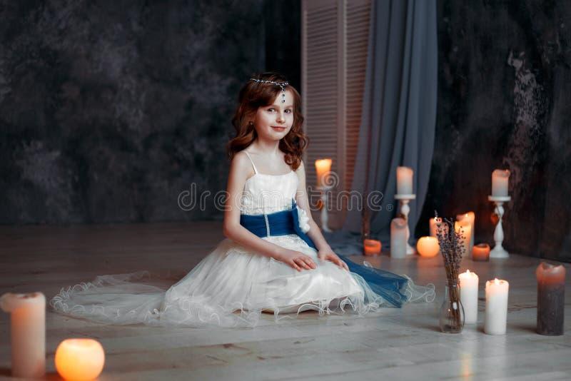 La niña en el vestido blanco en sitio con los niños de las velas ruega foto de archivo libre de regalías