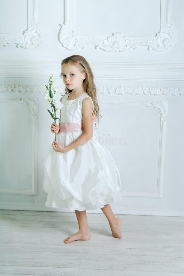 La niña en el vestido y la flor blancos está presentando fotografía de archivo