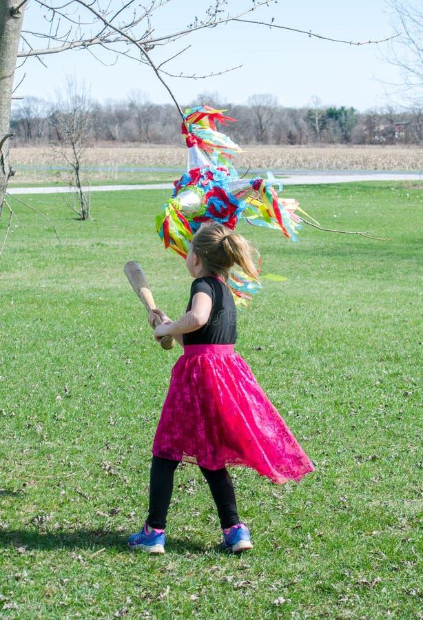La niña en rosa balancea en un pinata con un bate de béisbol de madera imagenes de archivo