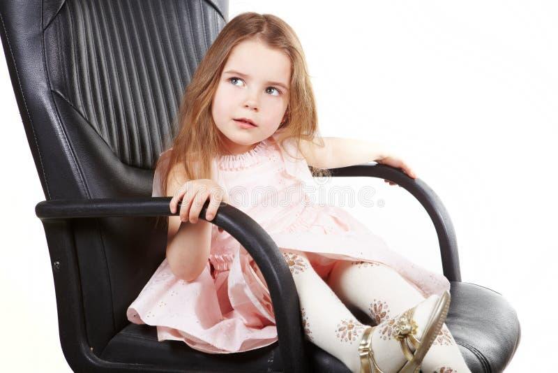 La niña en silla de la oficina y pide foto de archivo