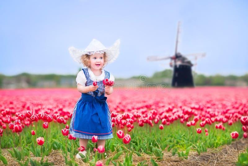 La niña en traje holandés en tulipanes coloca con el molino de viento fotos de archivo