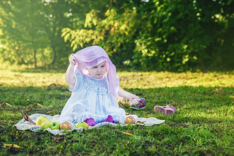 La niña en un vestido blanco y una bufanda rosada se sienta en un prado verde en el parque fotografía de archivo