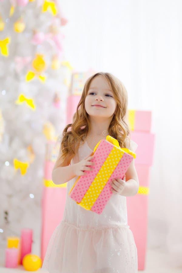 La niña en un vestido elegante presenta un regalo imagen de archivo
