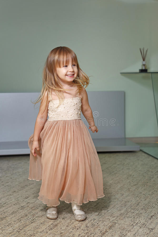 La niña en un vestido hermoso juega en casa fotografía de archivo