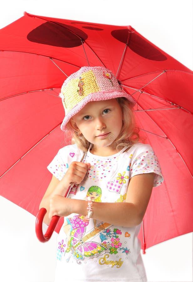 La niña encantadora con el paraguas rojo foto de archivo