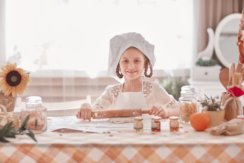 La niña encantadora en el sombrero del cocinero esculpe la pasta para las galletas foto de archivo libre de regalías