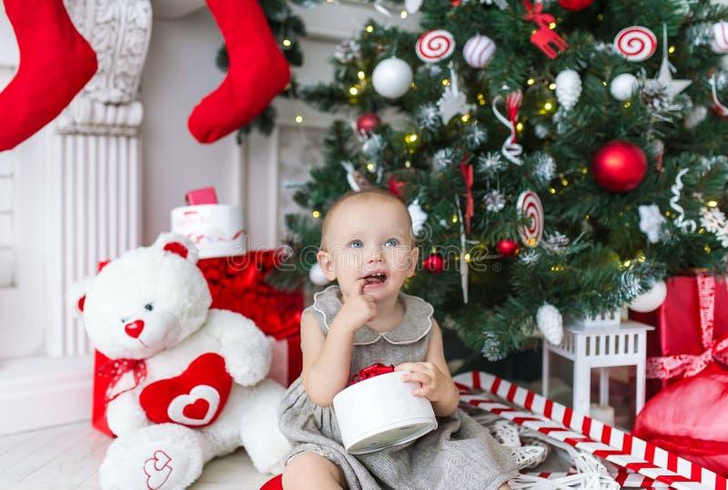 La niña encantadora se sienta debajo de un árbol de navidad con los regalos fotografía de archivo