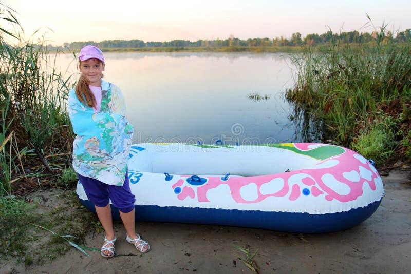 la niña envuelta en una toalla se coloca en la orilla del río cerca de un barco inflable fotografía de archivo