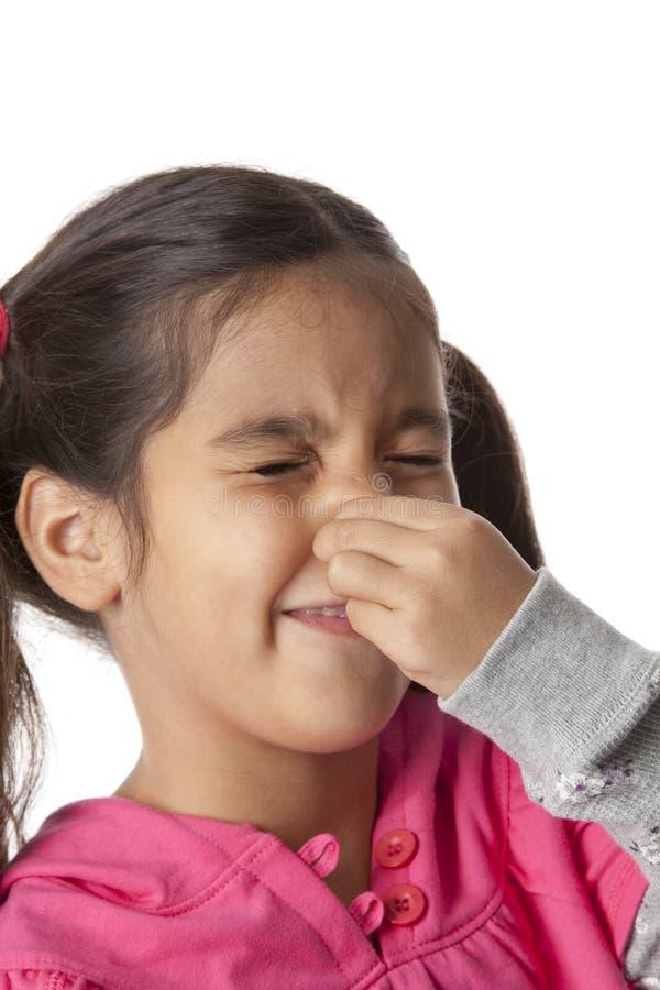 La niña es cerrada su nariz con sus dedos fotografía de archivo