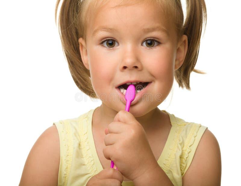 La niña es dientes de la limpieza usando el cepillo de dientes fotos de archivo