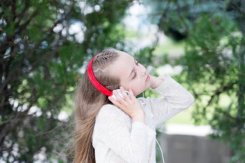 La niña escucha música en parque del verano Sonido de la melodía y mp3 El niño disfruta de música en los auriculares al aire libr fotografía de archivo