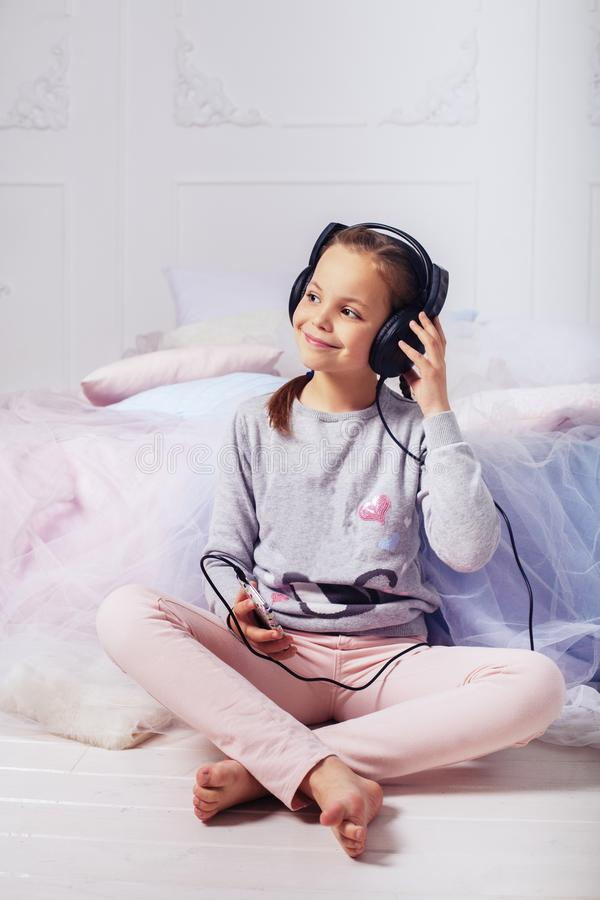 La niña escucha la música a través de los auriculares r fotografía de archivo