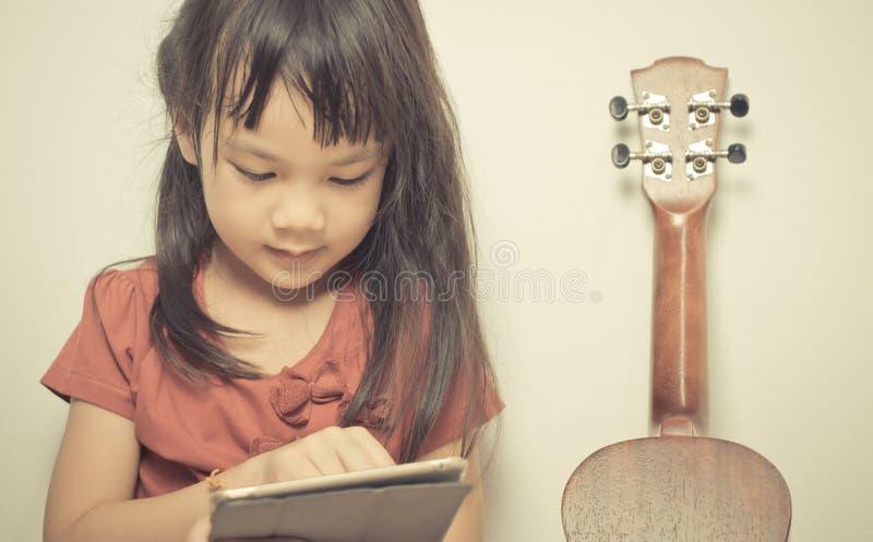 La niña está aprendiendo cómo tocar la guitarra usando su tableta foto de archivo libre de regalías