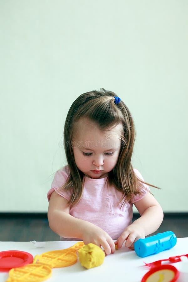 La niña está aprendiendo utilizar la pasta colorida interior, concepto del juego de actividad de la guardería imágenes de archivo libres de regalías