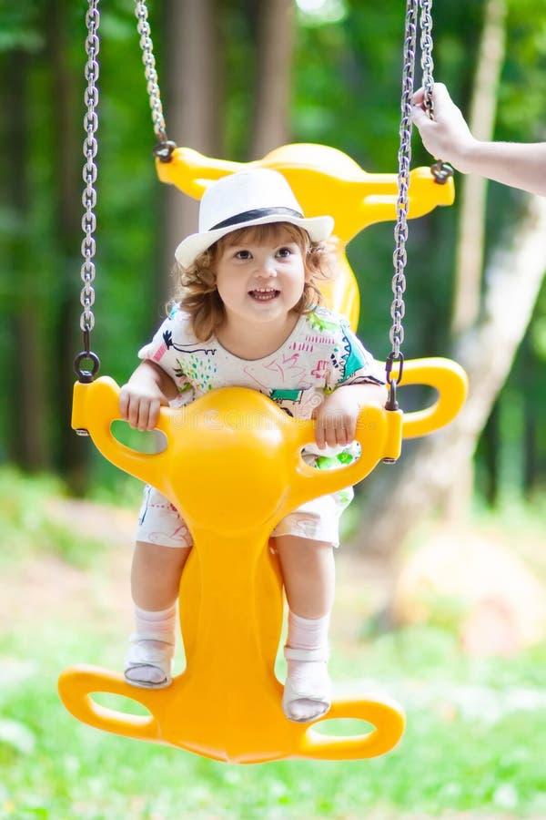 La niña está balanceando en la tierra del juego al aire libre, día soleado fotografía de archivo libre de regalías